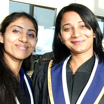 Two graduates smile at their Convocation ceremony